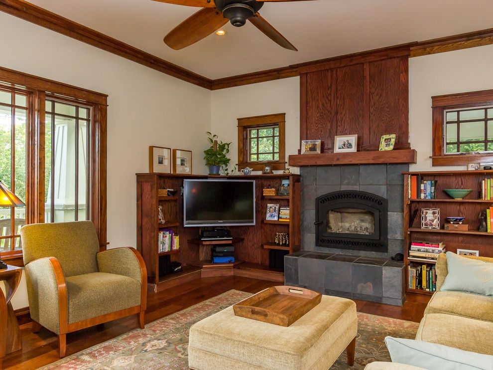 The Corner Tv Show   Craftsman Family Room Also Bookshelves Built Ins Ceiling Fan Dark Stained Wood Fireplace Frame and Panel Woodwork Greens Traditional Area Rug Upholstered Ottoman Wood Floor Wood Paneling Wood Stove