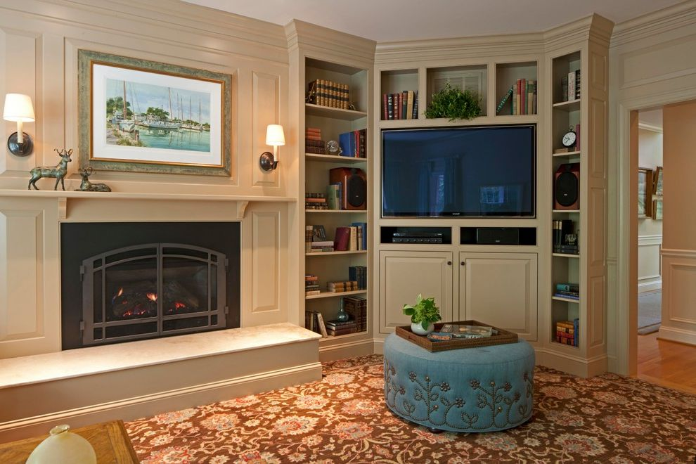 The Corner Tv Show   Transitional Family Room  and Area Rug Bookcases Bookshelves Cabinetry Corner Tv Cabinet Fireplace Nailhead Detail Ottoman Patterned Carpet Sconce Television Wall to Wall Carpet