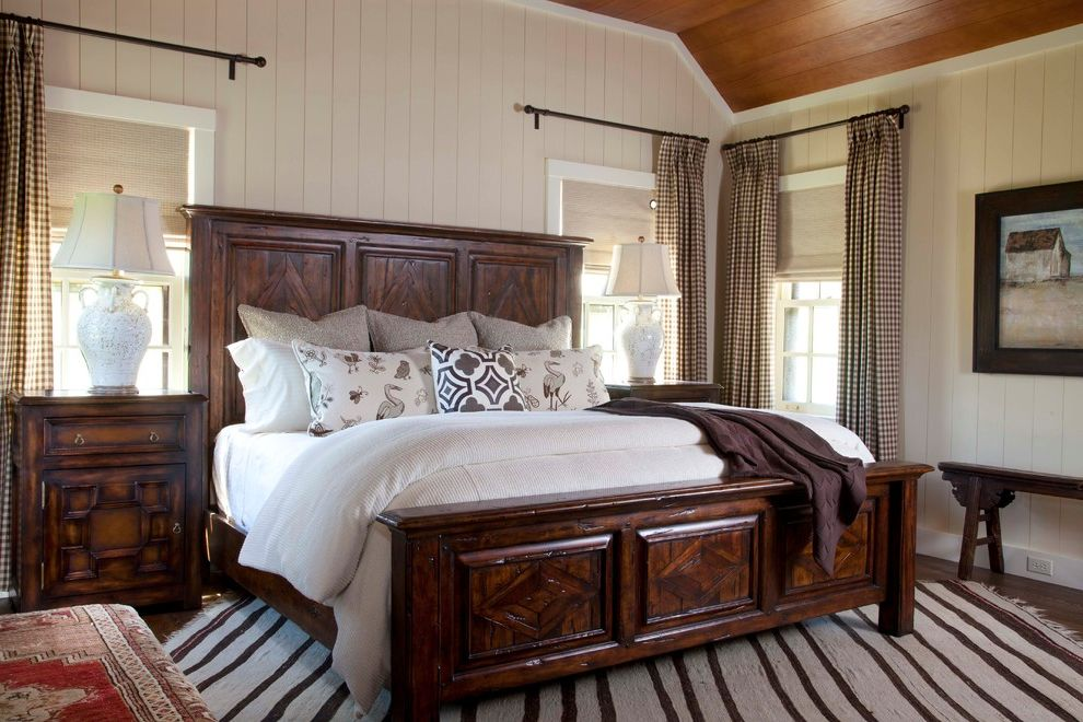 Ashley Furniture King Size Beds   Rustic Bedroom  and Area Rug Baseboards Bed Pillows Bedside Table Carved Bed Curtains Drapes Nightstand Sloped Ceiling Symmetry White Bedding White Wood Window Treatments Wood Bed Wood Paneling Wood Trim