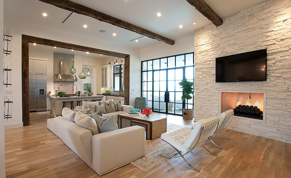 Intermountain Wood Products with Transitional Living Room Also Area Rug Beige Fireplace Patio Raised Firebox Seating Area Sectional Slant Ceilings Stone Wall Tall Windows White Leather Tufted Upholstery Wood Beams Wood Floors