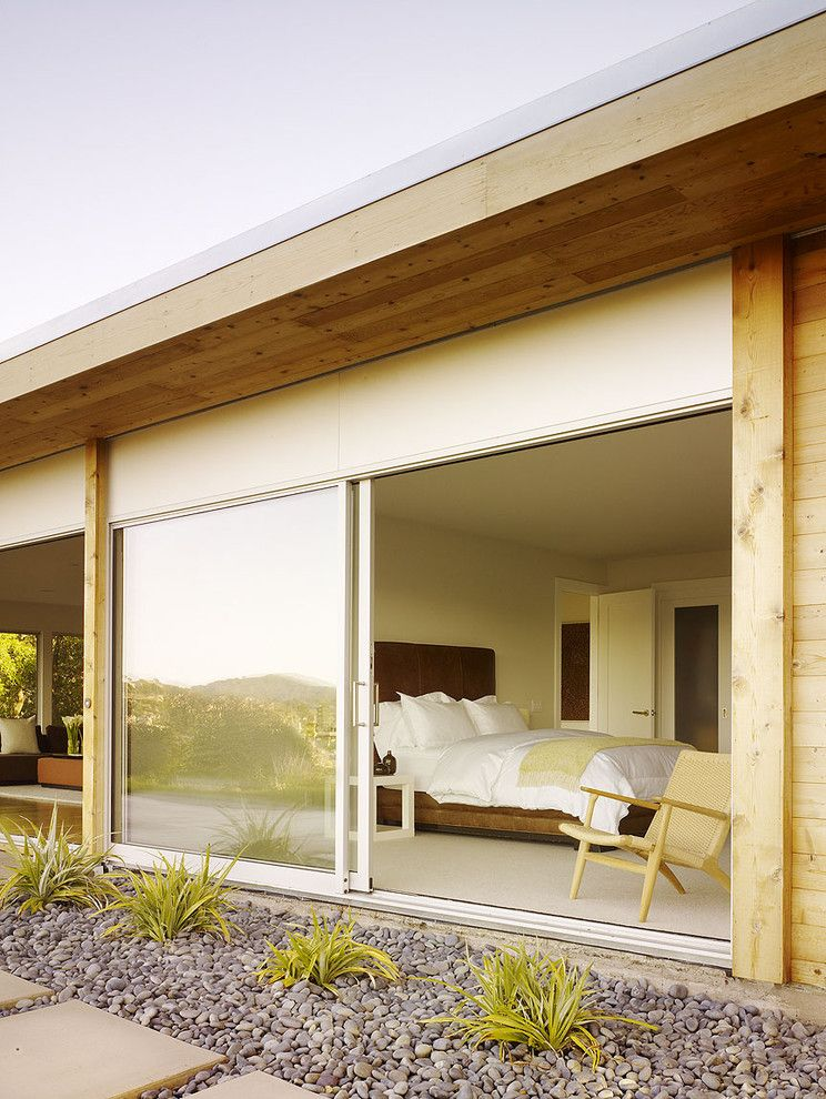 Sliding Window Air Conditioner with Modern Exterior  and Bed Brown Headboard Interior Design Landscape Architecture Minimal Overhang Pebbles Plants Residential Sliding Glass Door Square Pavers Wegner Chair Wood Planks