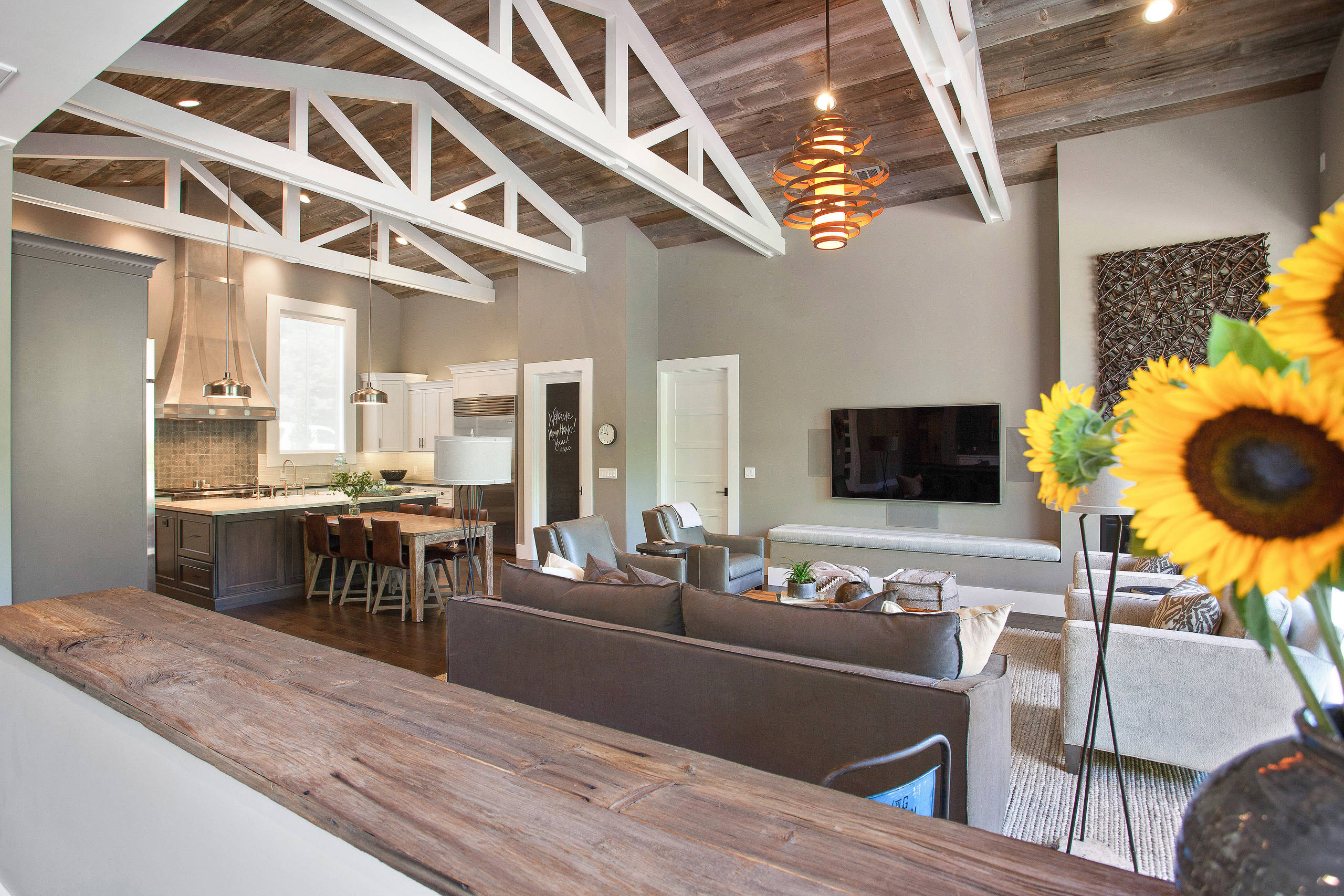 Open concept living room Farmhouse Family Room Barnwood ceiling with white trestles Corbett light fixture modern farmhouse