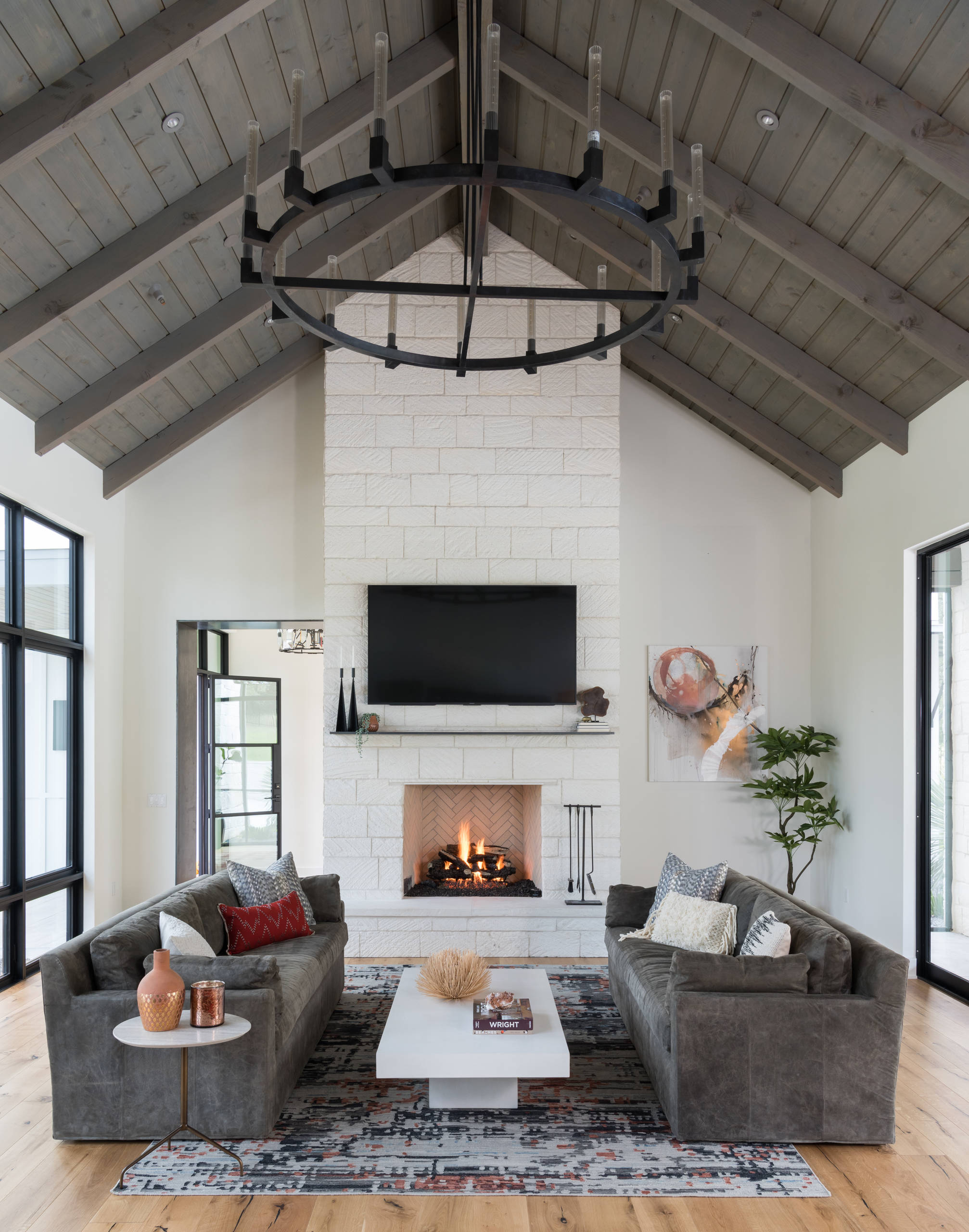 Floor to ceiling fireplace Farmhouse Living Room limestone fireplace metal chandelier metal mantle vaulted wood ceiling stone fireplace and a wall-mounted tv