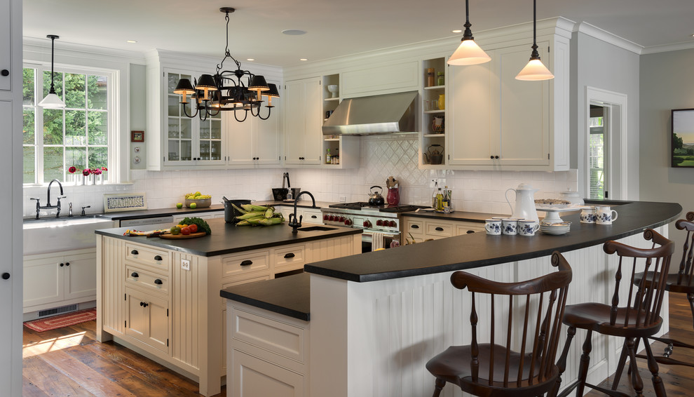 White cabinets dark countertops Traditional Kitchen farmhouse sink pendant light stainless steel appliances white tile backsplash