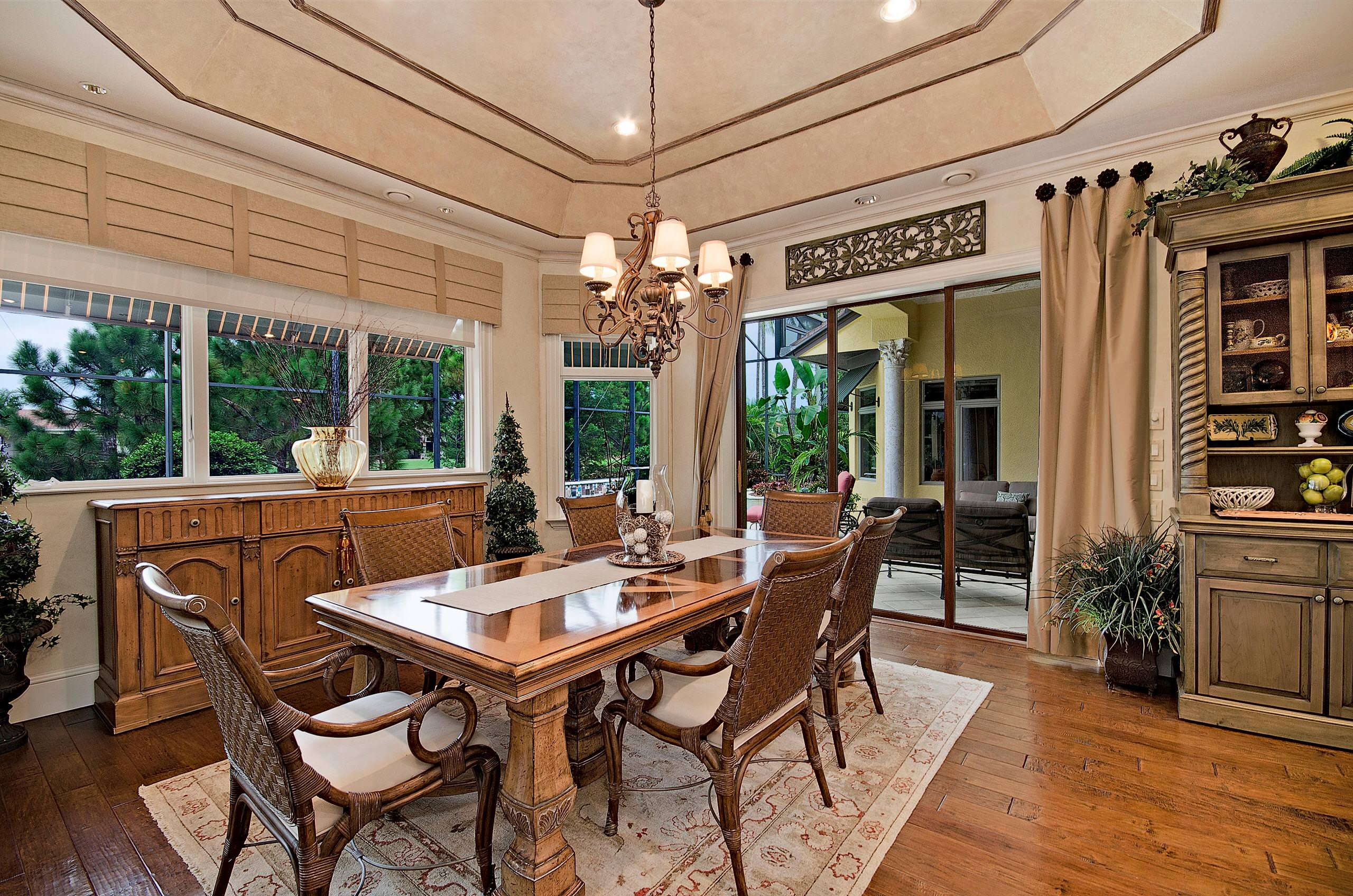 General contractor jacksonville fl Mediterranean Dining Room with area rug Art banquette brown chairs buffet centerpiece chandelier cornice curtains
