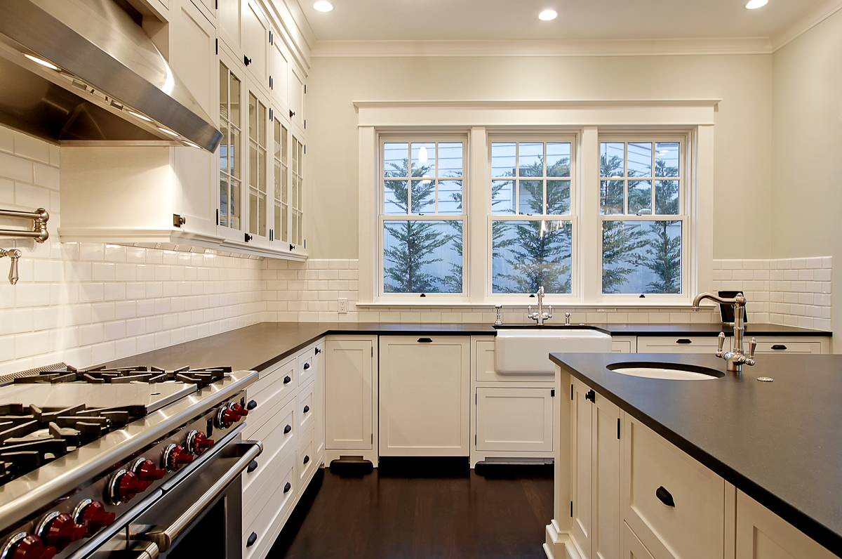 White kitchen cabinets with dark floors Traditional Kitchen farm sink glass front cabinets hood island pot filler subway tile backsplash