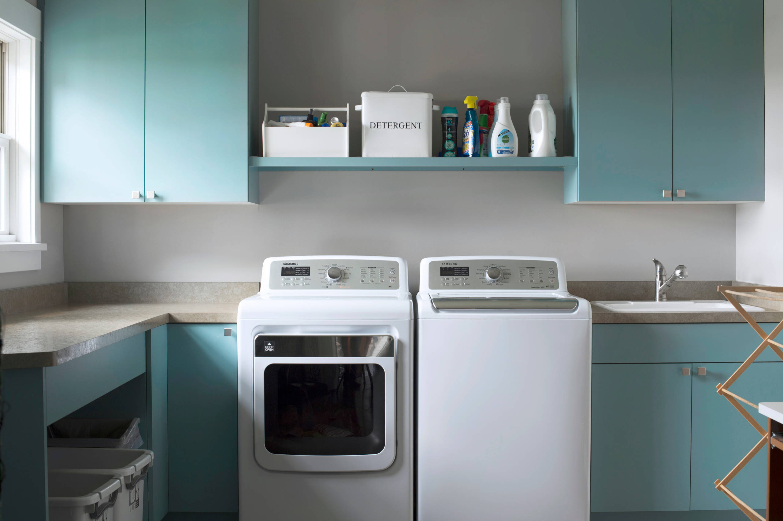 how much water does a washing machine use in Transitional Laundry Room bamboo rug ceiling lighting floating shelves floor tile front load washer and dryer